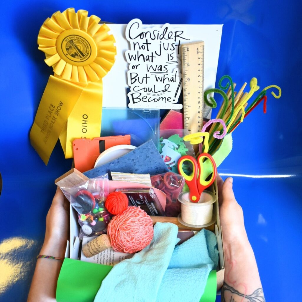 Upcycle craft box filled with materials like string, scissors, pipe-cleaners, 3rd place ribbon