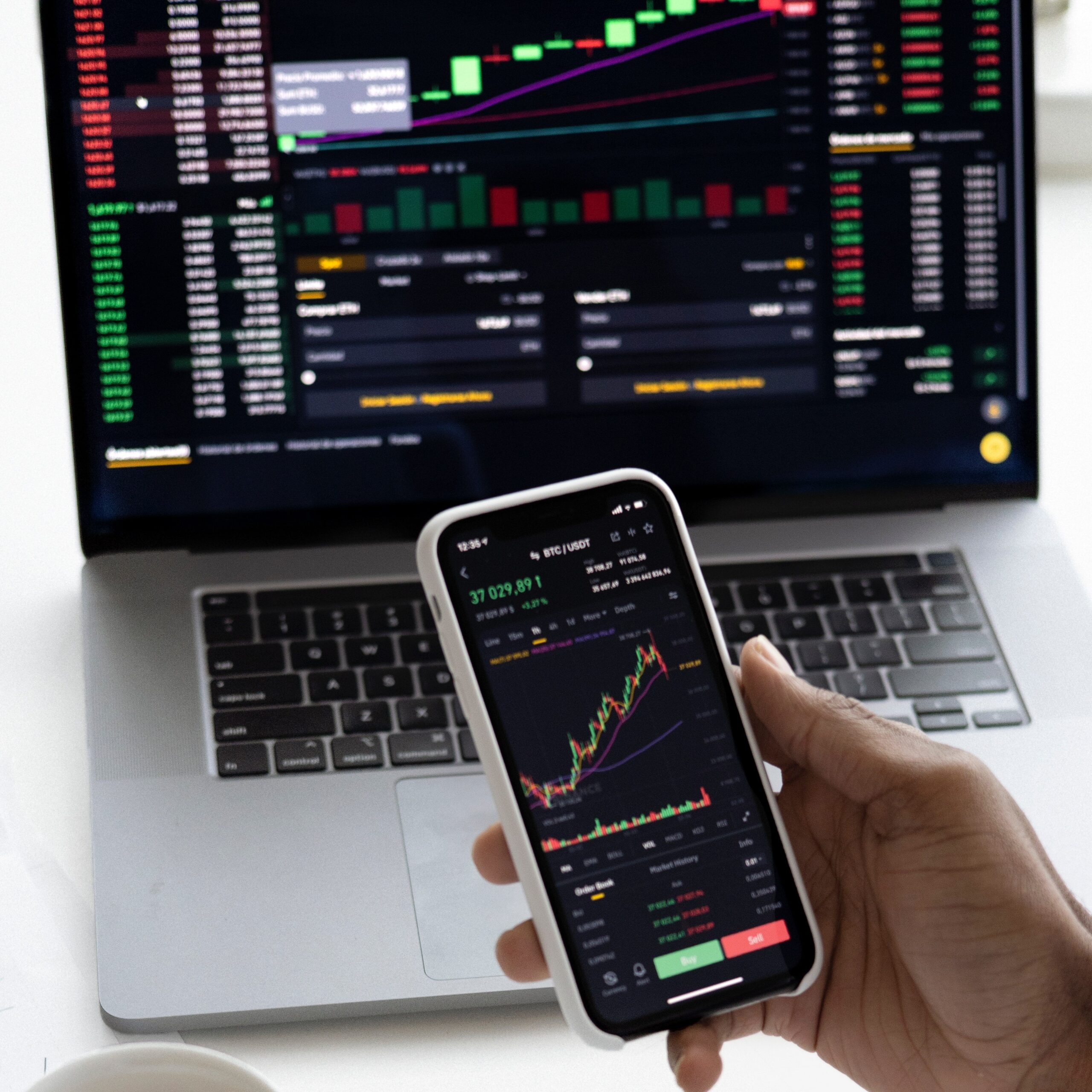 iPhone with stock market analysis in front of laptop with more stock market numbers